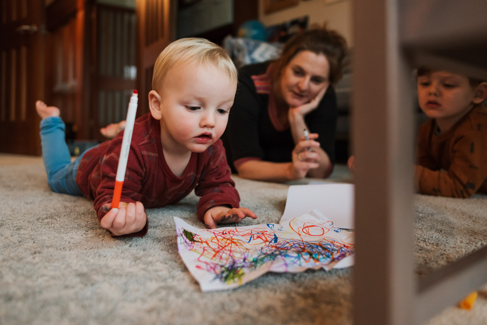 Unposed family photography, boy drawing on the floor, The Ginger Collective Photography