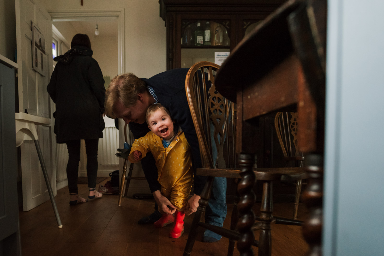 Documentary family photography, Dad putting wellies on boy, taken by The Ginger Collective photography Berkshire