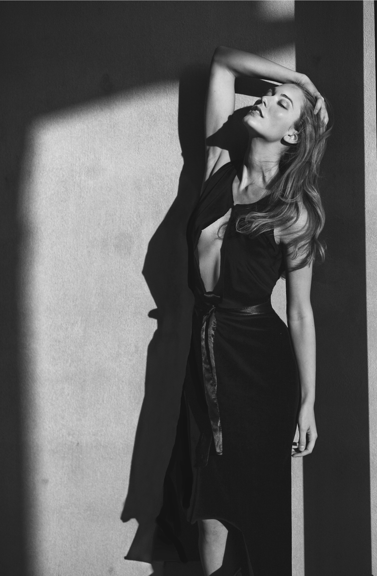 Black and white image of Jessamine holding forehead in model pose