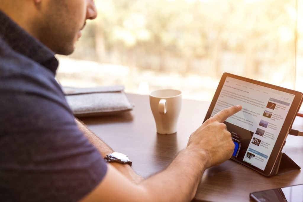 cropped-photo-of-man-sitting-at-table-with-coffee-mug-while-using-pointer-finger-to-navigate-on-propped-up-tablet