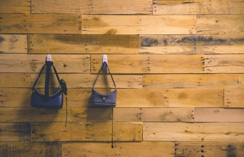 two-VR-headsets-hanging-from-hooks-on-rustic-wooden-wall