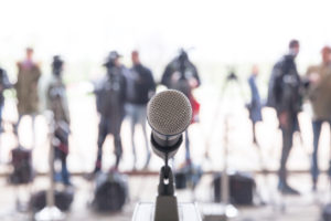 Microphone in focus against blurred camera operators and reporters at conference