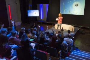 inspirational speaker on stage at work event