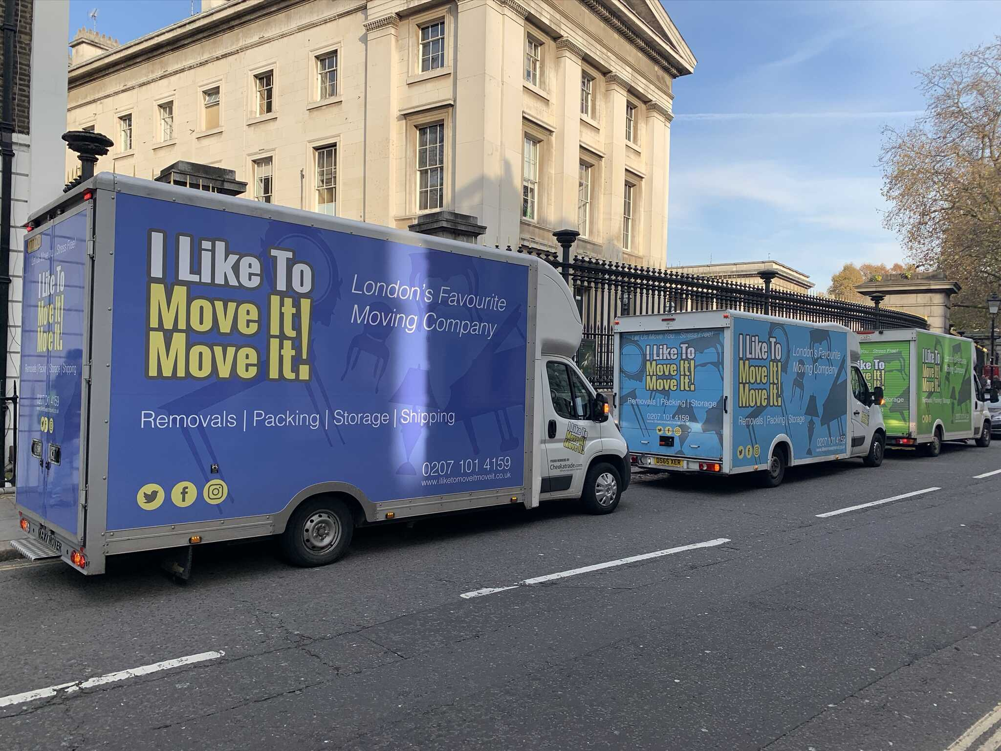 Three colourful branded removal vans parked outside a London listed building.