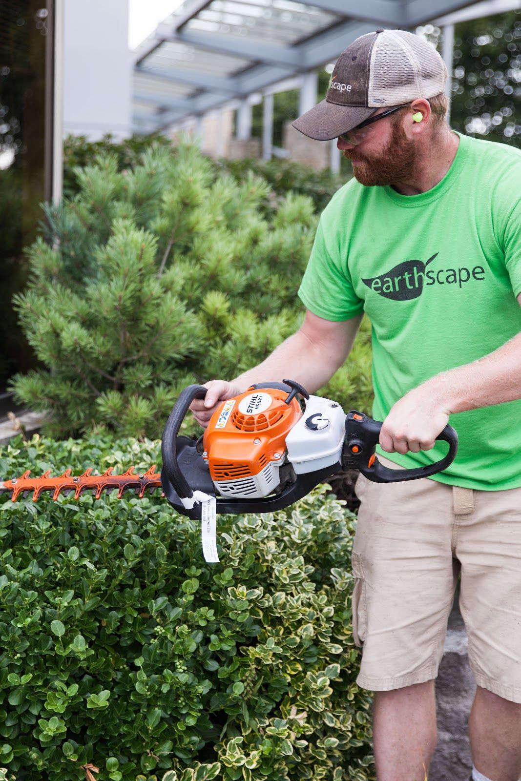 A landscaper trimming the bushes.