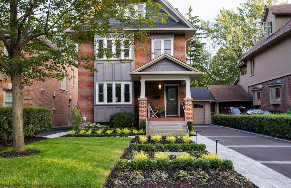 A three story brick home with a neatly organized front yard.