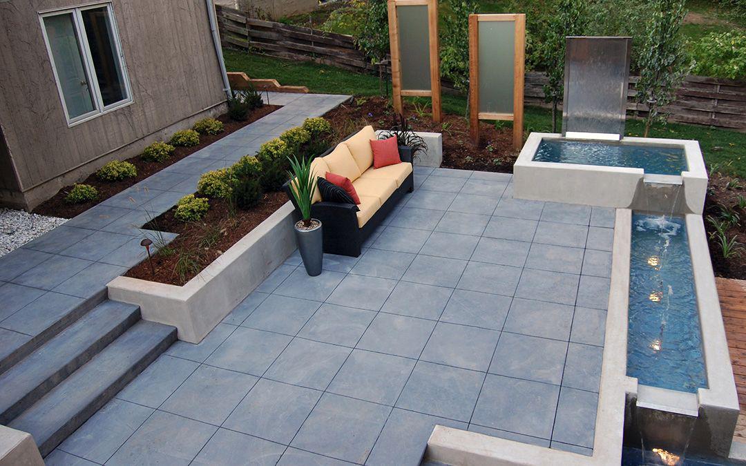 An open backyard patio with an outdoor sofa and a fountain.