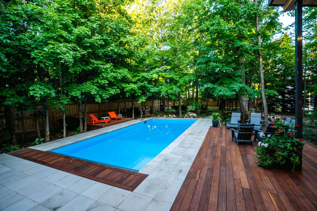 Backyard pool with stone walkway and large trees.