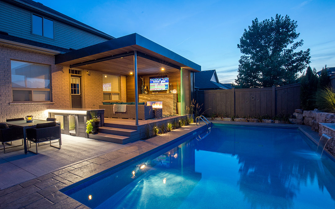 Backyard pool and an open and covered patio with a fireplace and sofa.