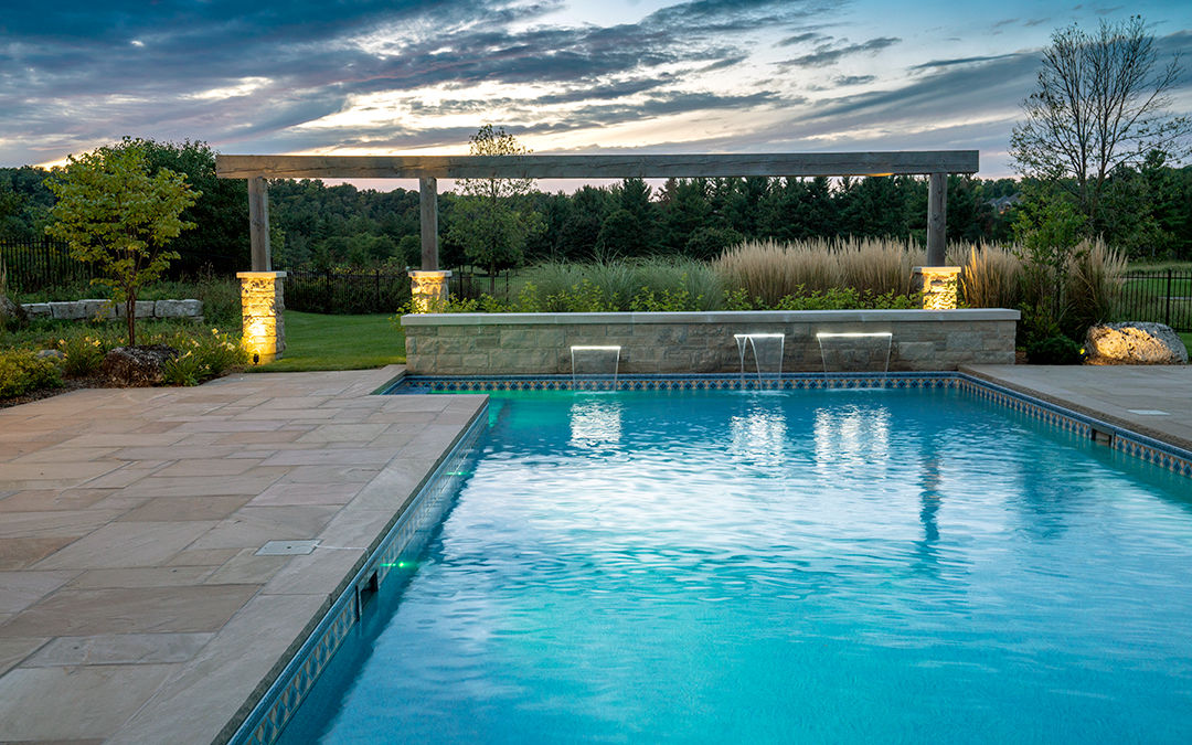 An outdoor pool with a large stone walkway and mini waterfall with landscape lighting and wooden arch.