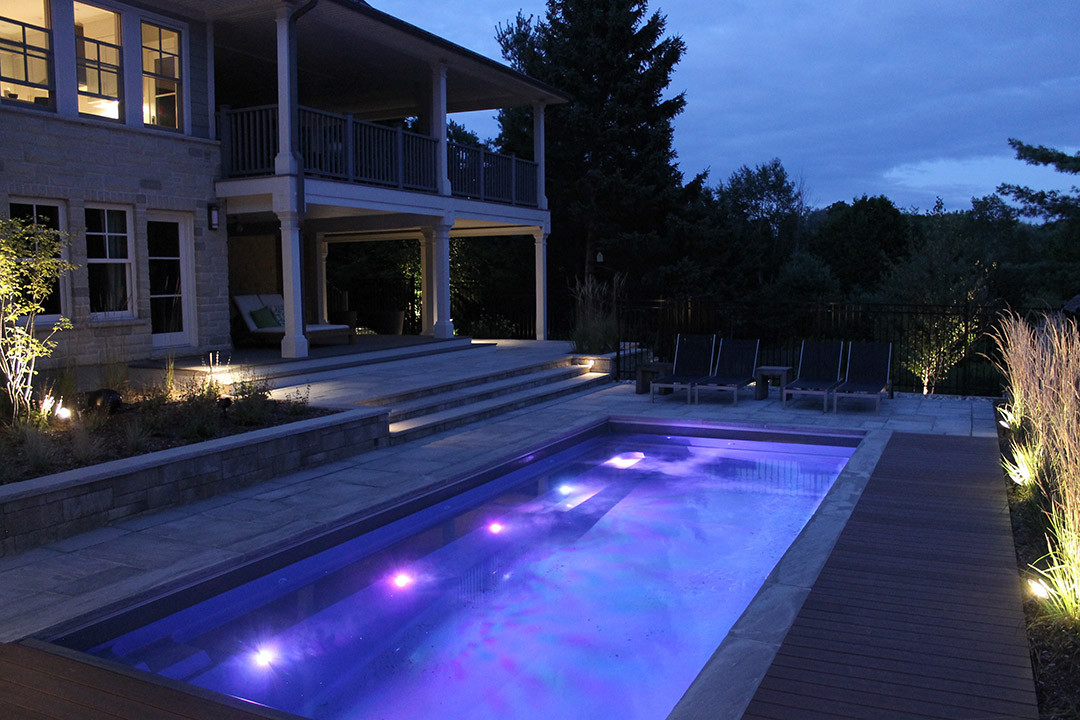 An outdoor pool with pool lights and light landscape.