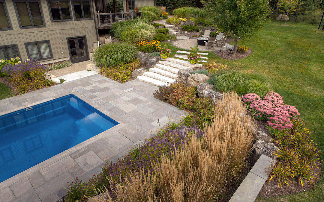 An aerial view of a small outdoor pool with a large garden.