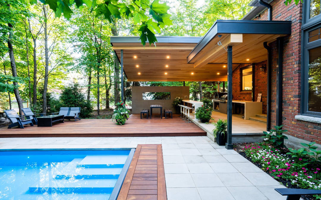 An open and partially covered extended patio with large trees and small flowers near an outdoor pool.