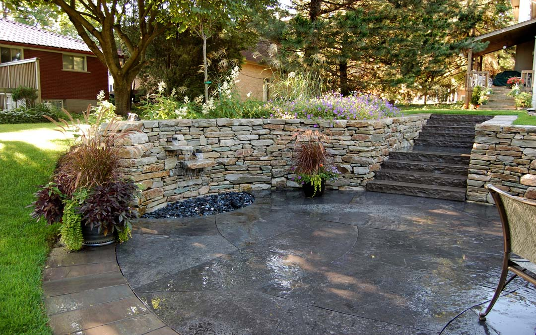 A beautiful drystone wall in a crescent shape featuring an elegant water feature.