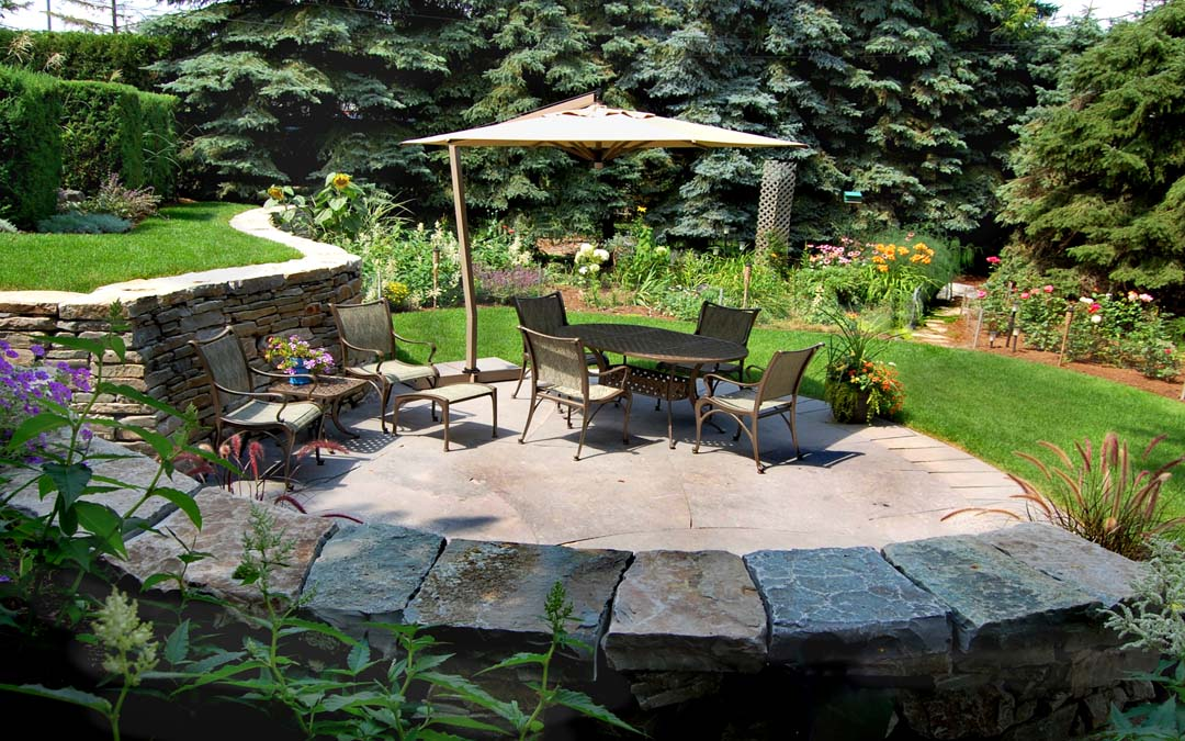 Ann outdoor sitting area made with flagstone flooring and drystone walls.