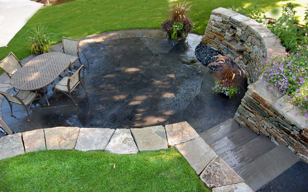 An aerial view of a patio with a flagstone walkway and drystone walls.