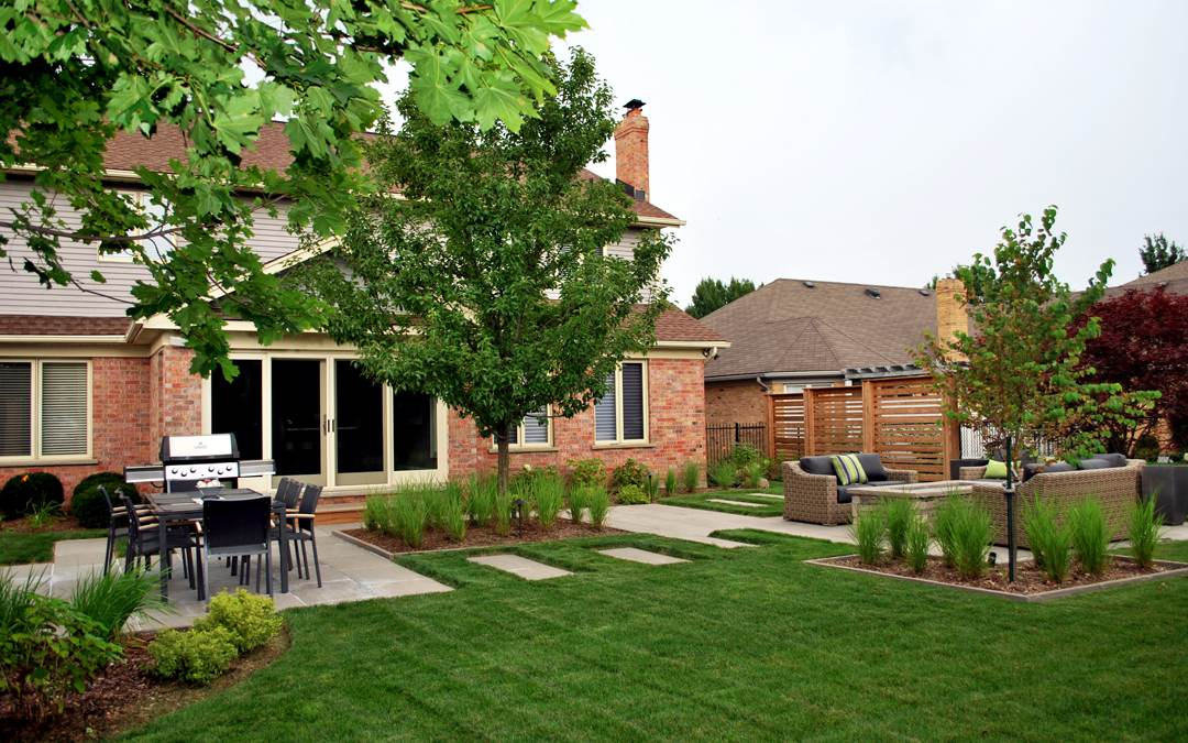 A beautiful lush backyard of a brick house with a patio and an outdoor sitting area.