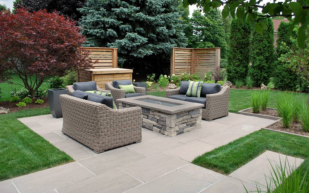 An outdoor area with a fire pit made of drystone and square cut flagstone walkway and patio.