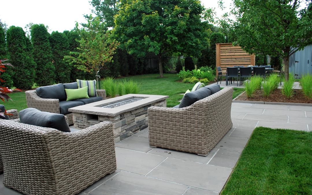 A patio made with square cut flagstone, a fire place and outdoor furniture.
