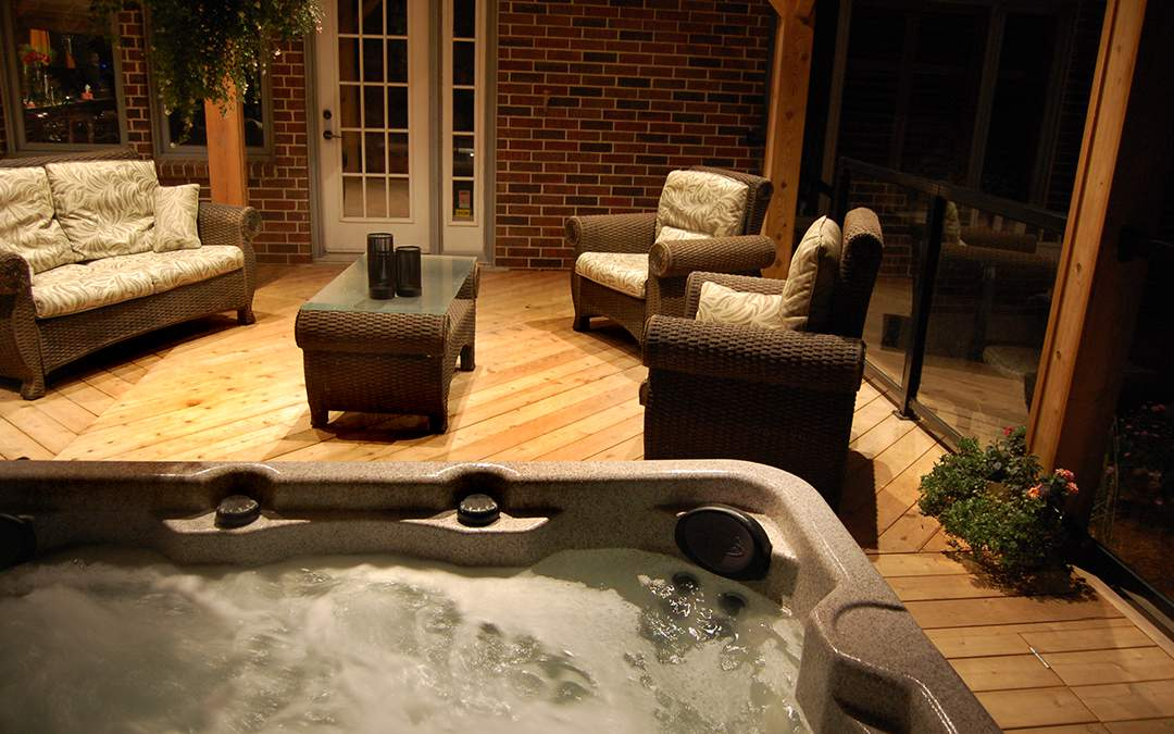 A bubbling hot top on a wooden deck with outdoor furniture.