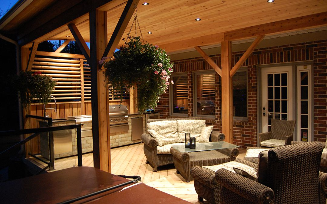 A relaxing outdoor living area with a kitchen, glass railings, outdoor furniture and a hot tub.