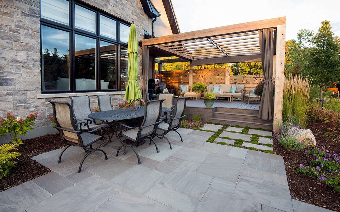 An outdoor dining table on top of a beautiful stone patio.