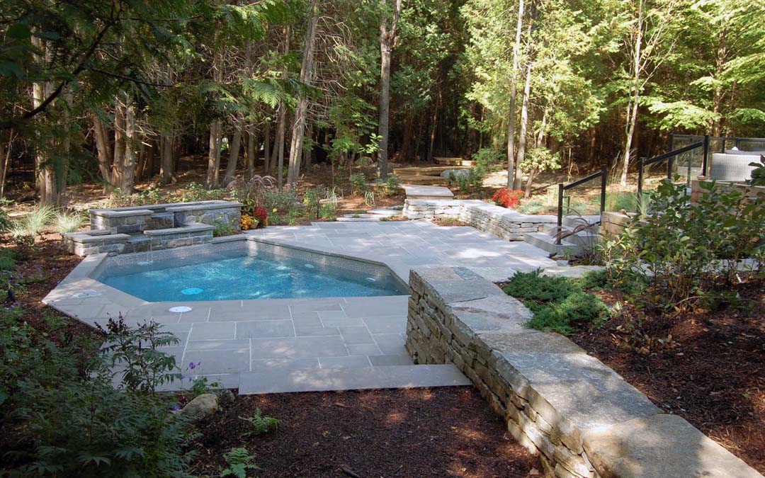 A custom built pool and cement patio with a water feature.