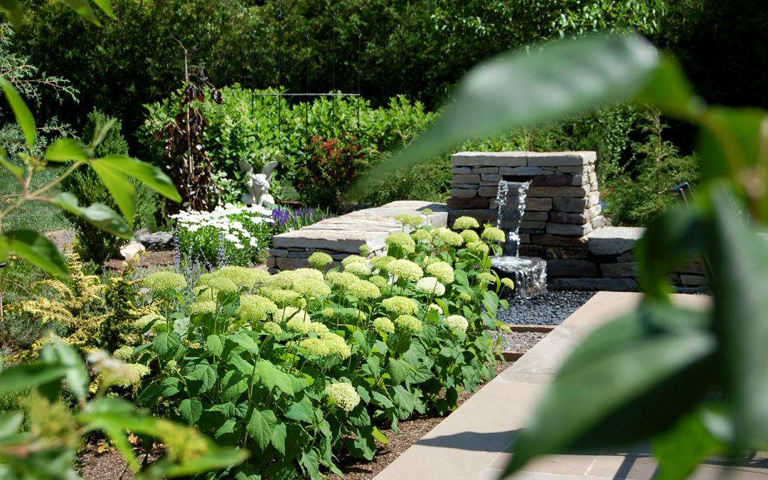 A stone garden with a water feature and a lush green garden.