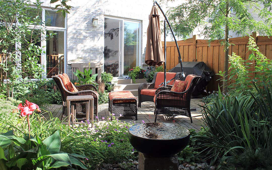 A secluded outdoor sitting area surrounded by a lush green garden and a relaxing water feature.