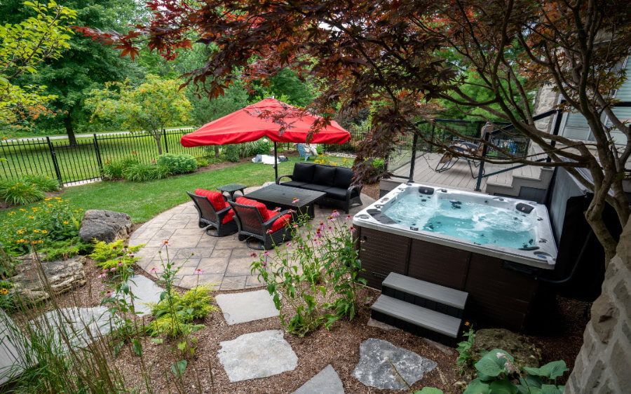 A secluded hot tub surrounded by a garden, stone walkway and a sitting area on top of a stone patio.