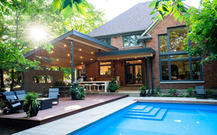 A pool near a stone patio and a covered outdoor dinning and living area.