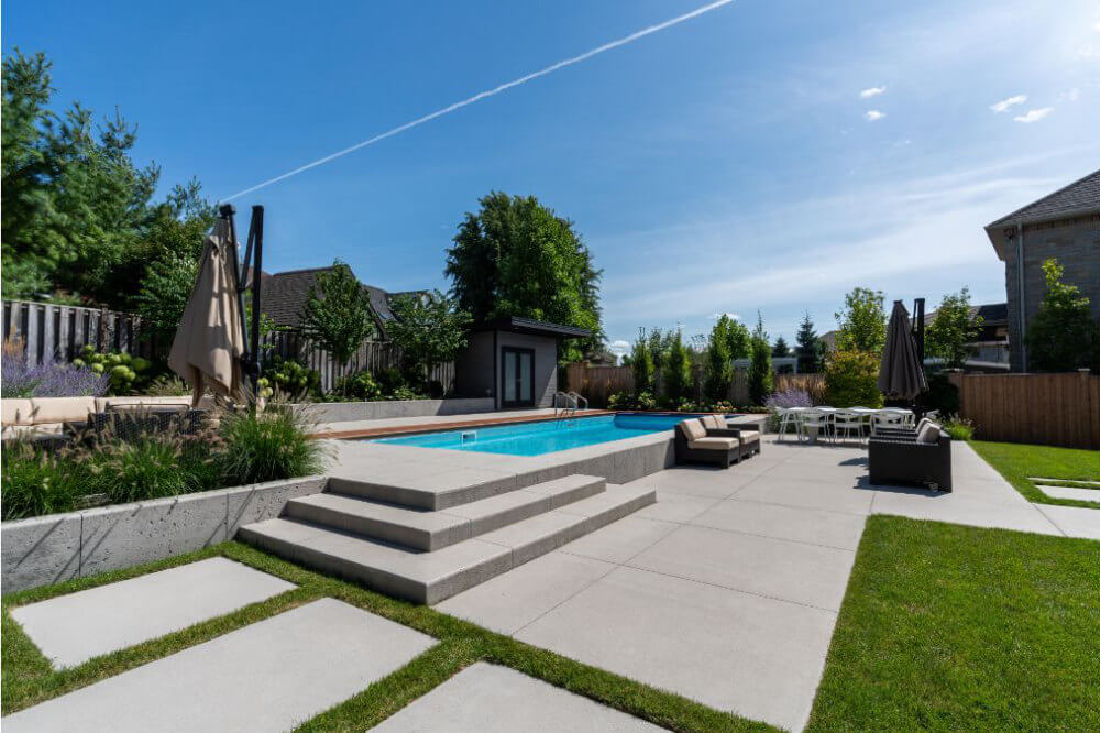 A smooth cement patio and poolside deck with a elegant stairs leading to the pool.