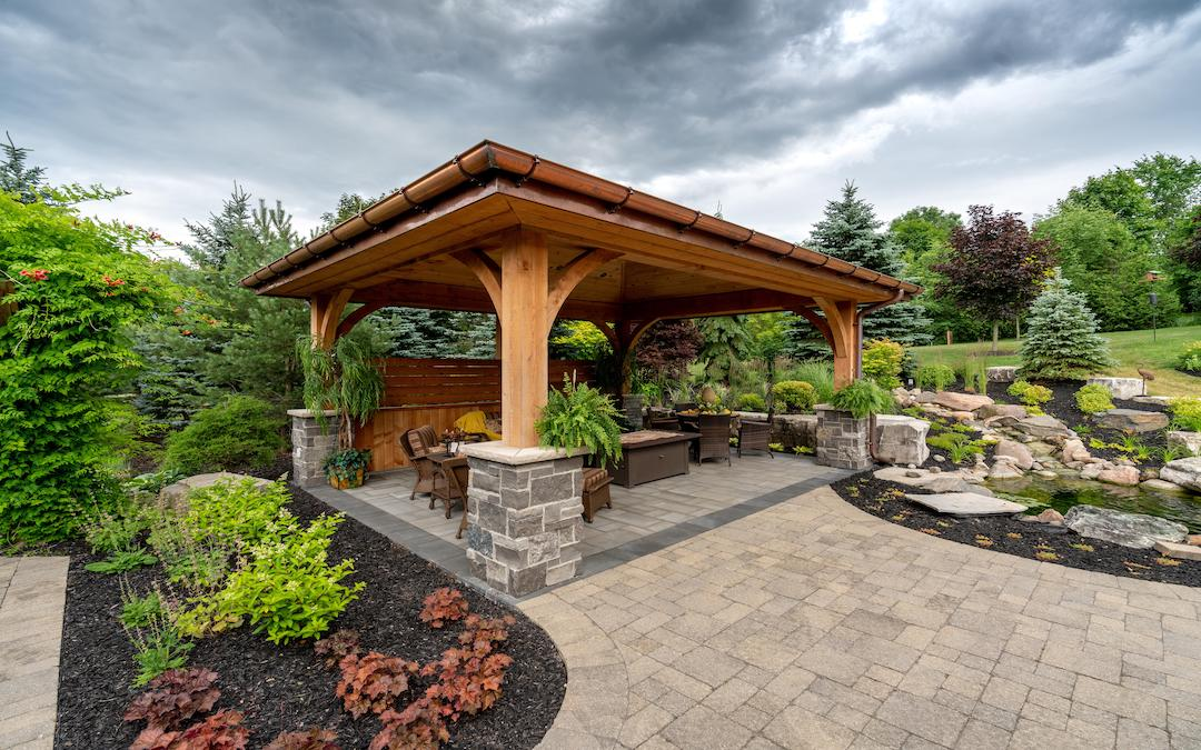An amazing covered outdoor timber living area. with a stone pathway and gardens leading up to it.