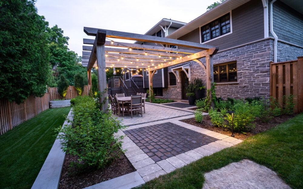 A rustic themed outdoor sitting area with a stone patio and hanging lights.