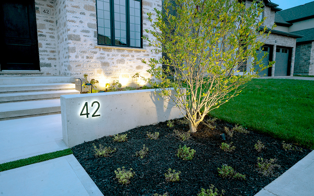A curbside garden and a cement wall with a house number.
