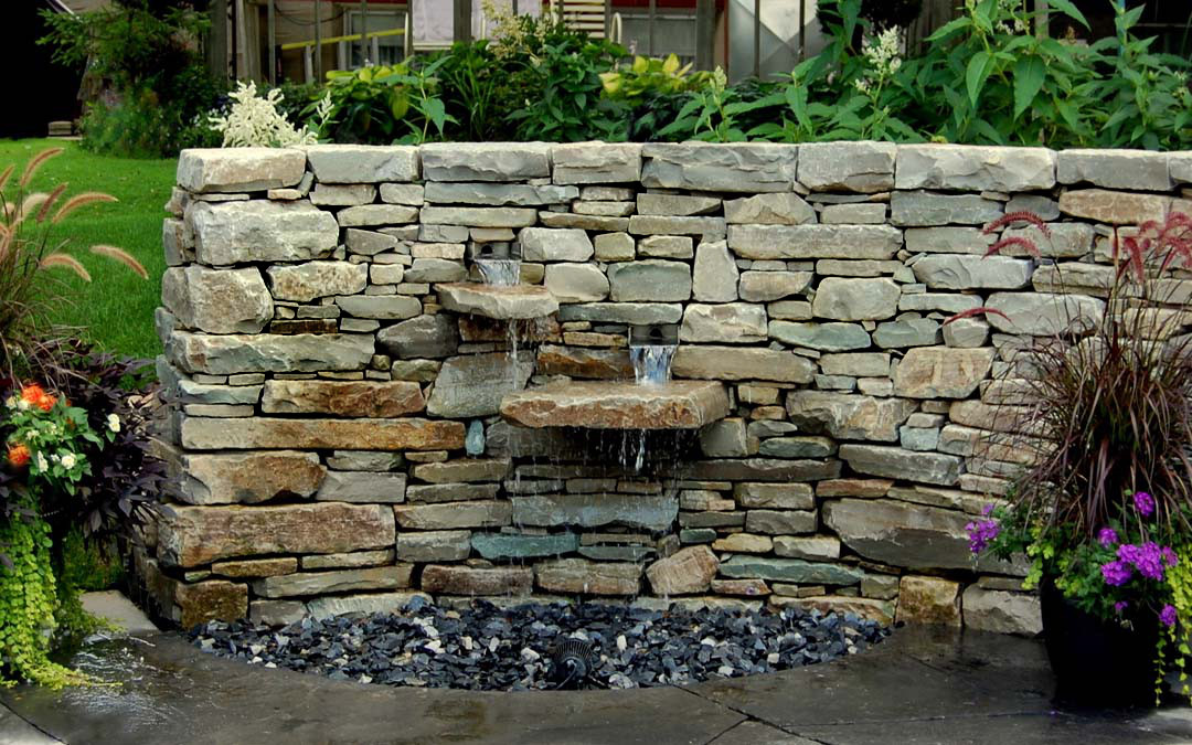 A curved drystone wall with a water feature.