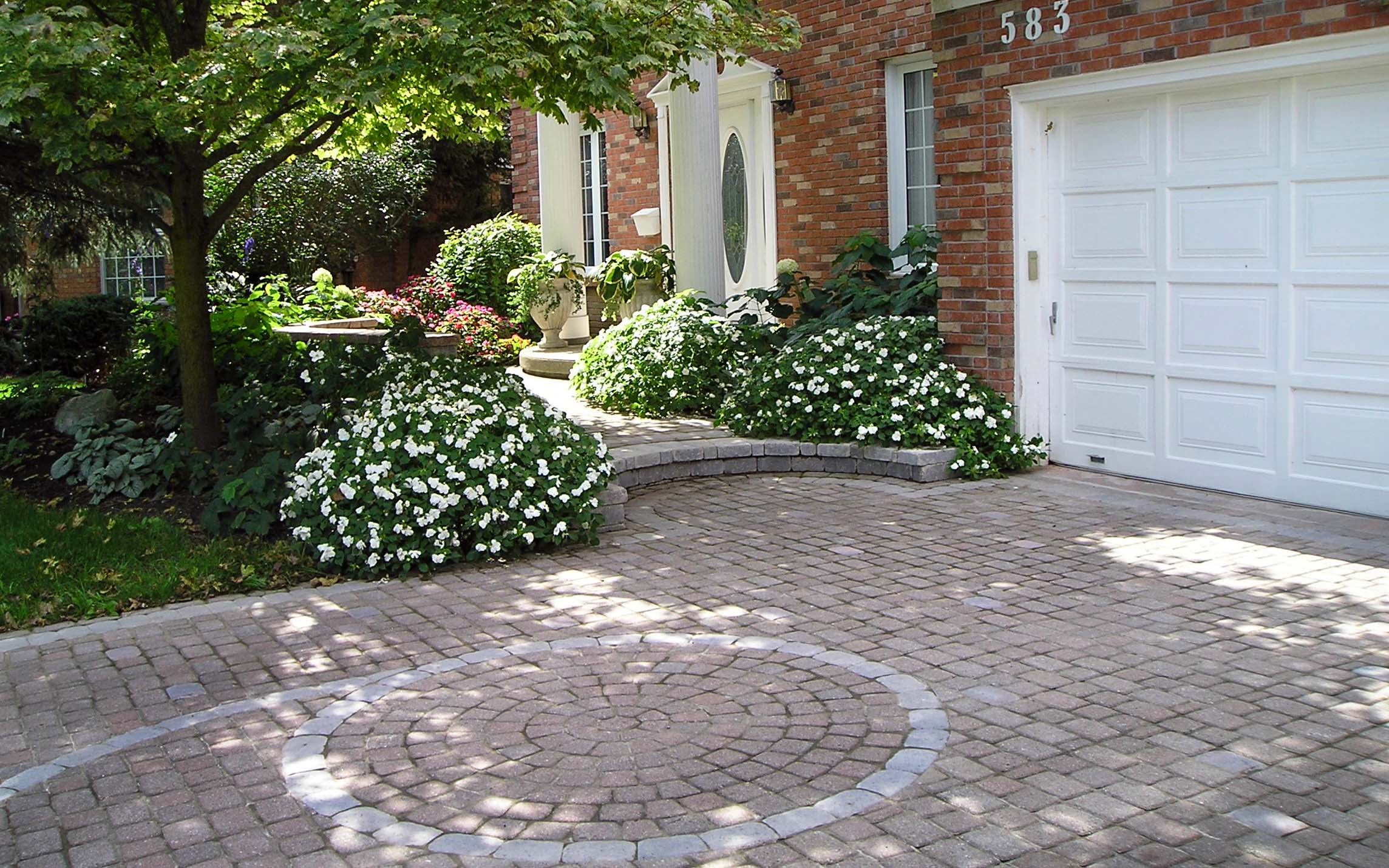 A beautiful stone driveway and entrance lined with a lush green garden.