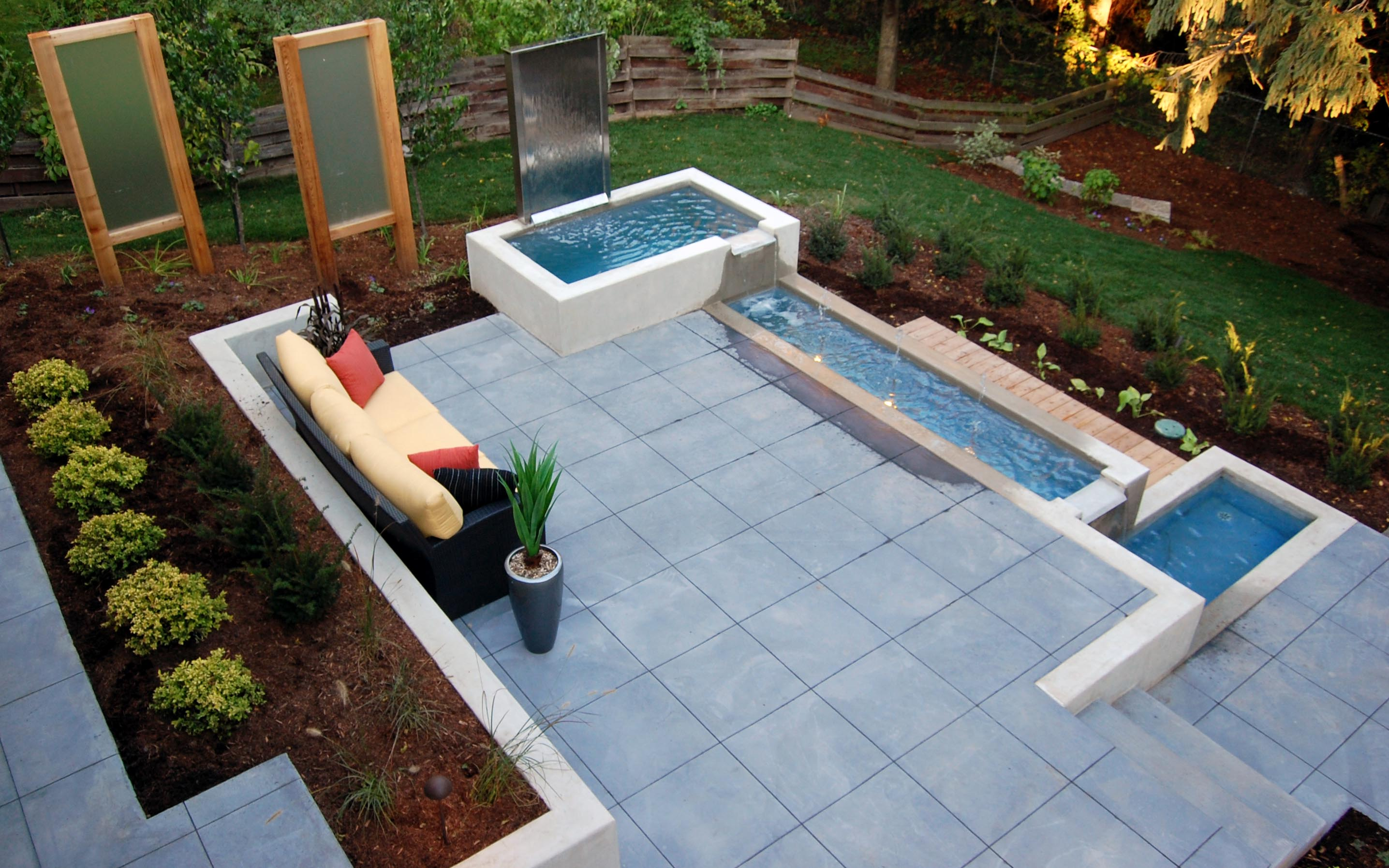 A peaceful outdoor siting area with a cement patio and a relaxing water feature.
