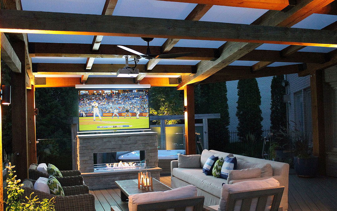 An outdoor covered entertainment area complete with a sitting area, fire place and a TV.