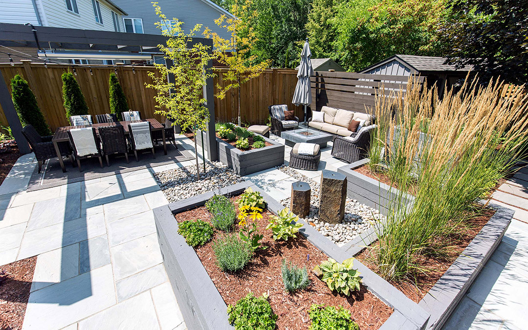 A calm relaxing outdoor area with stone patio, timber fence and a beautiful raised garden.