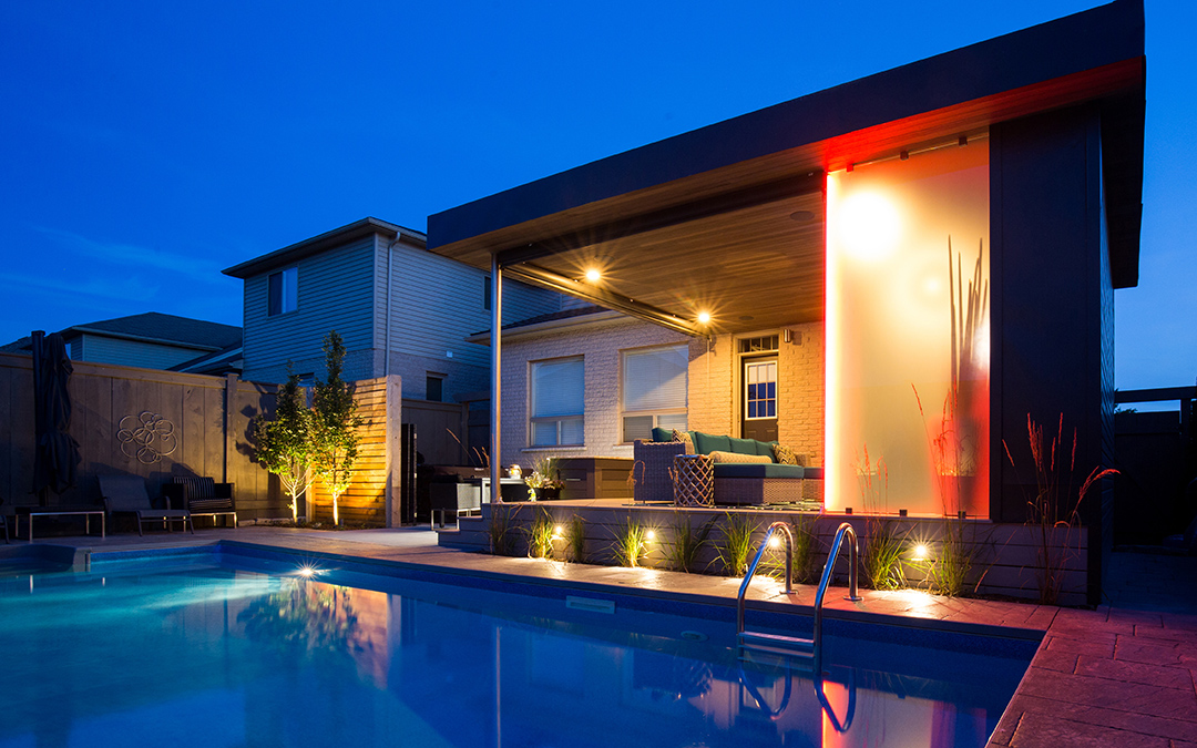 A large pool lined with accent lighting and an outdoor living area.