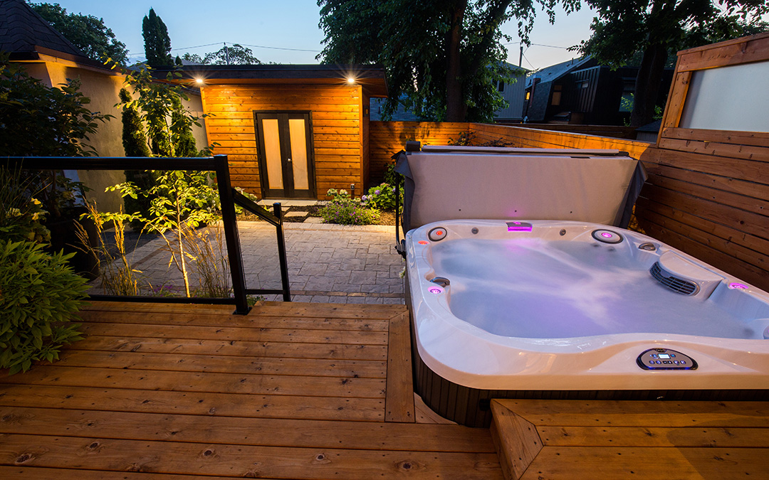 A small hot tub on a timber deck with glass railings leading down to a stone patio.
