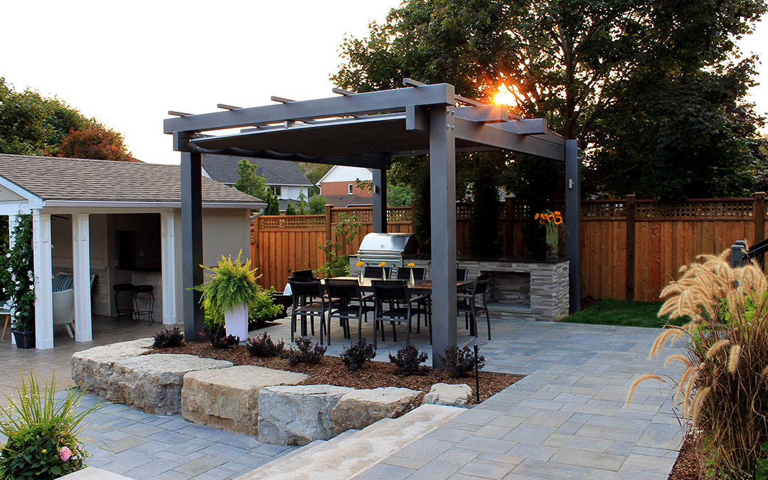 A beautiful stone patio with small garden and an outdoor kitchen.
