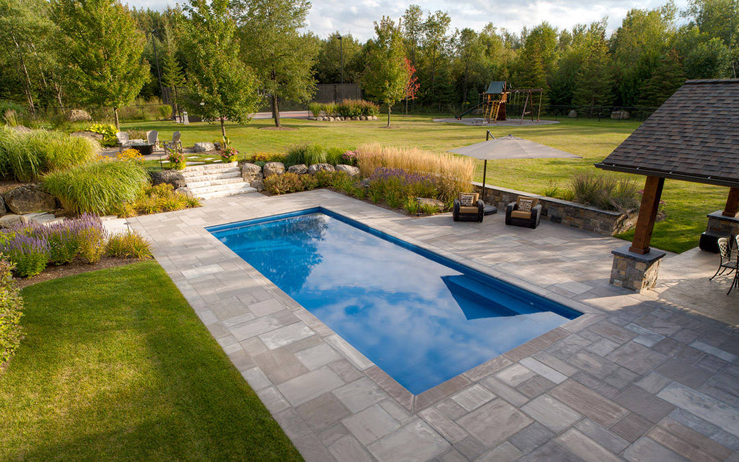 A large open backyard with a pool which is outlined by a stone patio.