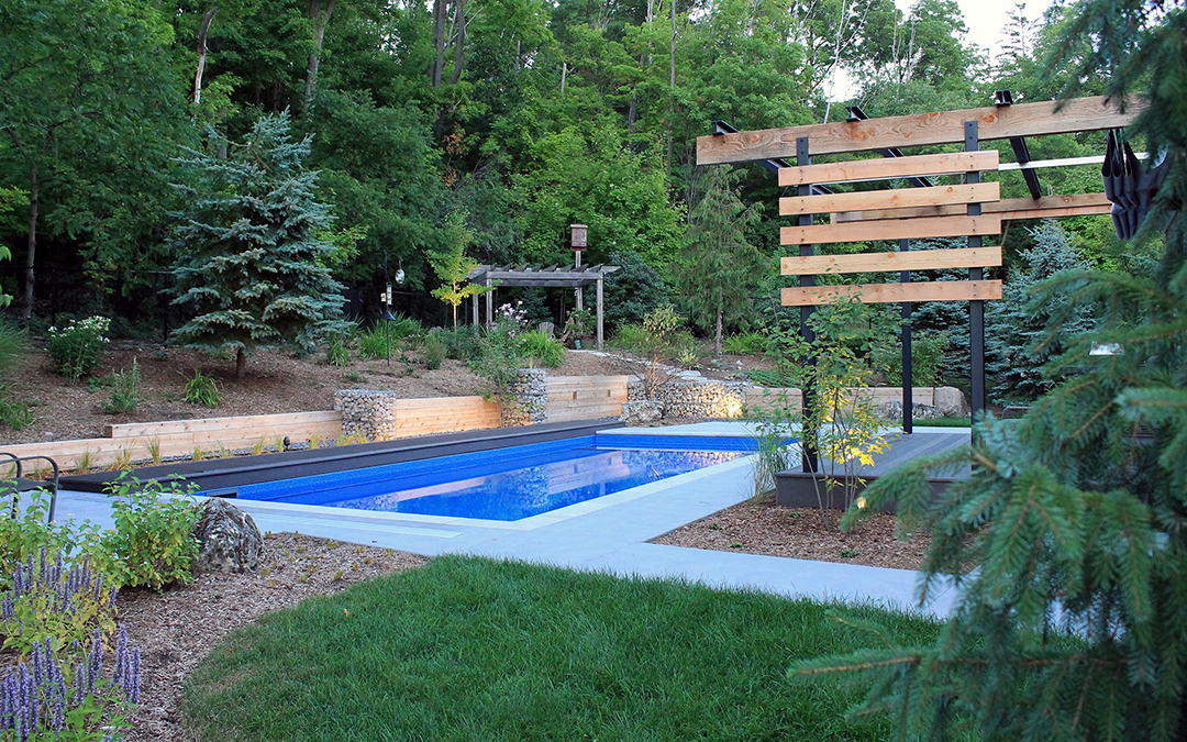 A beautiful swimming area surrounded by trees and a nice timber wall.