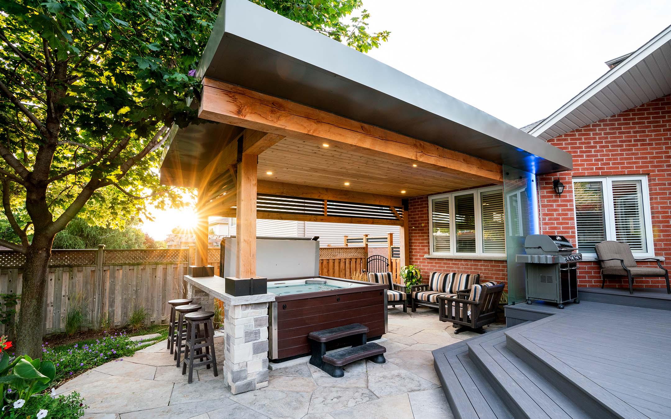 An outdoor living area with a hot tub and a bar table.