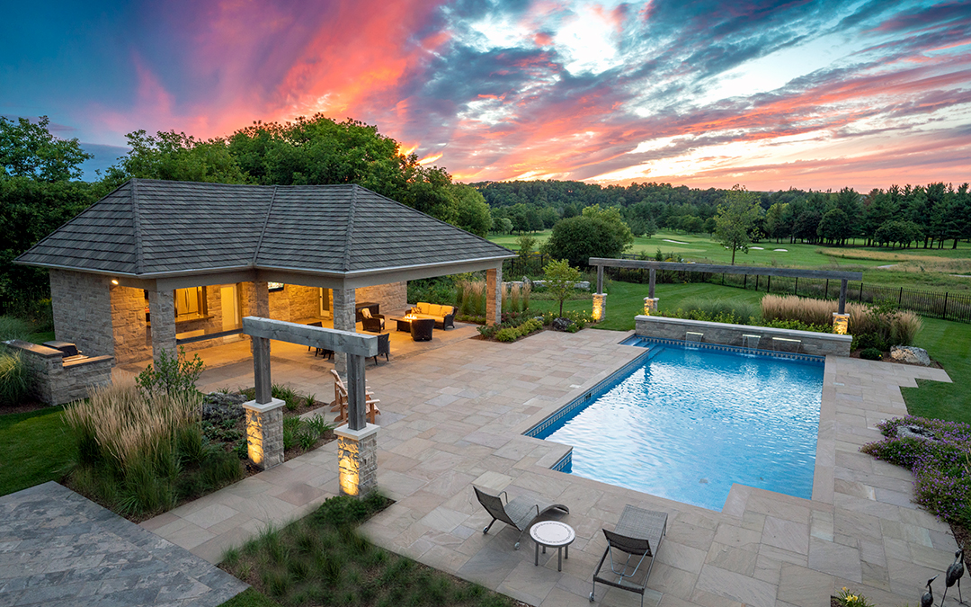 A beautiful sunset over a pool and a large pool house with stone patio and a covered outdoor sitting area.