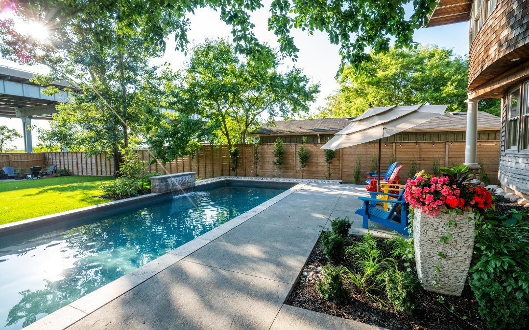 A skinny but long pool with a cement patio and a small garden.