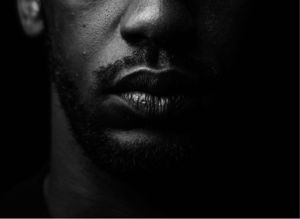 Dark and moody portrait of a Black man that has been cropped from his nose to his chin.