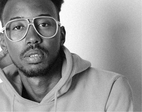 Black and white portrait of a young adult Black man wearing large glasses and a hoodie.